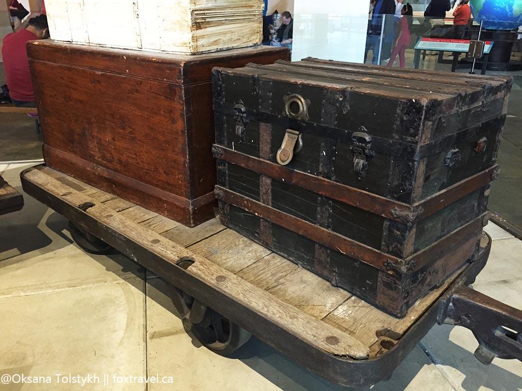 грудой реальных чемоданов и сундуков, оставленных тут иммигрантами